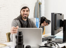 Young attractive press photographer holding photographic camera viewing his work on editor office desk Royalty Free Stock Photos