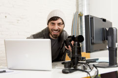 Young attractive press photographer holding photographic camera viewing his work on editor office desk Royalty Free Stock Photo