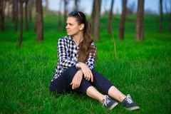 Young attractive pretty woman sitting on grass resting. In sunny weather in field on bright green background. Spring nature. Lifestyle, leisure concept Royalty Free Stock Image