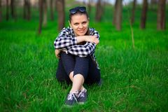Young attractive pretty woman sitting on grass resting. In sunny weather in field on bright green background. Spring nature. Lifestyle, leisure concept Royalty Free Stock Photo