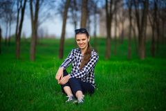 Young attractive pretty woman sitting on grass resting. In sunny weather in field on bright green background. Spring nature. Lifestyle, leisure concept Royalty Free Stock Images
