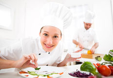 Young attractive professional chef cooking in his kitchen Royalty Free Stock Images