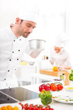 Young attractive professional chef cooking in his kitchen Royalty Free Stock Photo