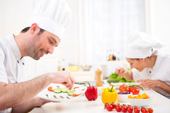 Young attractive professional chef cooking in his kitchen Stock Image