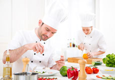 Young attractive professional chef cooking in his kitchen Stock Images