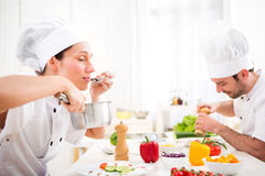 Young attractive professional chef tasting sauce Stock Images
