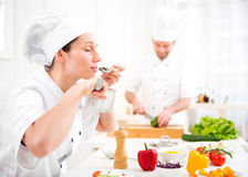 Young attractive professional chef tasting sauce Stock Photo