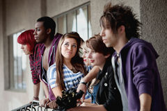 Young attractive punk girl poses. The camera focuses on an attractive young punk girl who poses for the camera while her friends look away into the distance Royalty Free Stock Image