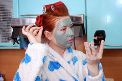 The young attractive red girl with a clay face pack looks in a pocket mirror in kitchen. Stock Images