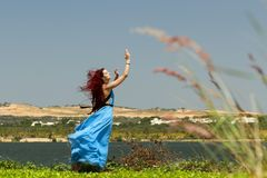 Young attractive red hair woman in blue dress dansing on green field royalty free stock photo