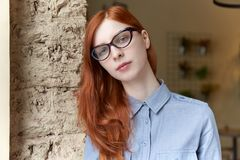 Young attractive red-haired girl with glasses and blue shirt stu royalty free stock photos
