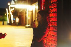 Red-haired girl smokes an electronic cigarette. Young attractive red-haired girl smokes an e-cigarette. She walks down street. Evening city lights and signs stock photography
