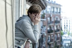 Young attractive unhappy lonely woman with depression looking sad on the balcony at home. Young attractive,red haired, unhappy lonely caucasian woman with stock image