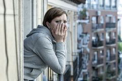 Young attractive unhappy depressed lonely woman looking hopeless ans sad on the balcony at home. Young attractive,red haired, unhappy lonely caucasian woman with Royalty Free Stock Photos
