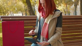 Girl with foxy hair sitting on bench in sunny weather use tablet and makes an online order stock video footage