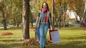 A girl with foxy hair walks through the park with purchases in multi-colored paper bags stock footage
