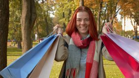 Happy girl with foxy hair walks in the park with purchases in multi-colored paper bags and rejoices stock video