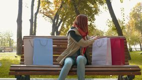 A girl with foxy hair sitting on a bench in the park and reviewing her purchases in paper bags after going to store stock video footage