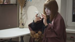 Young attractive red-haired woman uses the application on the smartphone in kitchen at night. Young attractive red-haired woman uses the application on the stock video footage