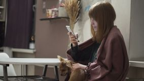 Young attractive red-haired woman uses the application on the smartphone in kitchen at night. Young attractive red-haired woman uses the application on the stock footage