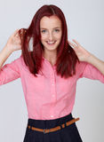 Young attractive redhead female in pink shirt Royalty Free Stock Images