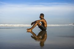Young attractive and relaxed black afro American man with fit body and muscular back sitting on beach sand enjoying beautiful view stock image