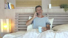 Young attractive 30s man with blue eyes happy and relaxed at home in bed talking with mobile phone smiling stock footage