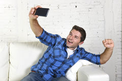 Young attractive 30s man taking selfie picture or self video with mobile phone at home sitting on couch smiling happy Royalty Free Stock Photography
