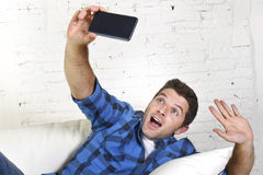 Young attractive 30s man taking selfie picture or self video with mobile phone at home sitting on couch smiling happy Royalty Free Stock Image