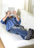 Young attractive 30s man using digital tablet pad lying on couch at home networking looking relaxed Stock Photos