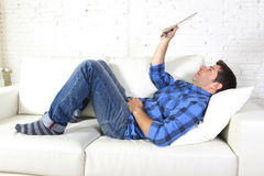 Young attractive 30s man using digital tablet pad lying on couch at home networking looking relaxed Royalty Free Stock Photos