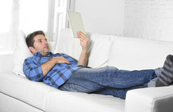 Young attractive 30s man using digital tablet pad lying on couch at home networking looking relaxed. Young attractive 30s man using digital tablet pad lying on Royalty Free Stock Photography