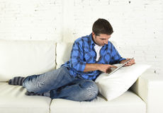 Young attractive 30s man using digital tablet pad lying on couch at home networking looking relaxed Royalty Free Stock Images