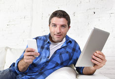 Young attractive 30s man using mobile phone and digital tablet pad on couch smiling happy Royalty Free Stock Photo
