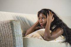 Young attractive and sad black African American woman lying depressed at home sofa couch feeling anxious and frustrated suffering. Depression problem and royalty free stock photo