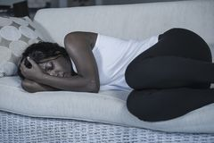 Young attractive and sad black African American woman lying depressed at home sofa couch feeling anxious and frustrated suffering. Depression problem and stock photography