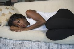 Young attractive and sad black African American woman lying depressed at home sofa couch feeling anxious and frustrated suffering. Depression problem and royalty free stock photography