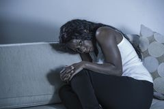 Young attractive and sad black African American woman sitting depressed at home sofa couch feeling anxious and frustrated sufferin. Young attractive and sad royalty free stock photos