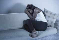 Young attractive and sad black African American woman sitting depressed at home sofa couch feeling anxious and frustrated sufferin. Young attractive and sad stock photo