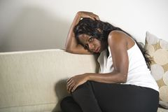 Young attractive and sad black African American woman sitting depressed at home sofa couch feeling anxious and frustrated sufferin. Young attractive and sad royalty free stock image