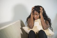 Attractive and sad black African American woman sitting depressed at home sofa couch feeling anxious and frustrated suffering mens. Young attractive and sad stock photo