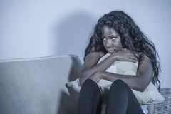 Attractive and sad black African American woman sitting depressed at home sofa couch feeling anxious and frustrated suffering mens. Young attractive and sad royalty free stock image