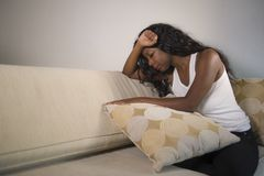 Young attractive and sad black African American woman sitting depressed at home sofa couch feeling anxious and frustrated sufferin. G depression problem and stock photo
