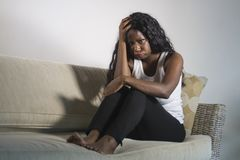 Young attractive and sad black African American woman sitting depressed at home sofa couch feeling anxious and frustrated sufferin. G depression problem and stock photography