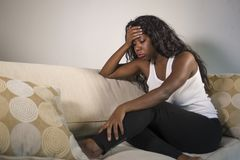 Young attractive and sad black African American woman sitting depressed at home sofa couch feeling anxious and frustrated sufferin royalty free stock photo