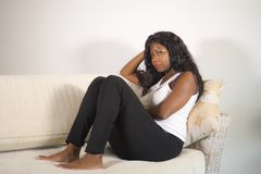 Young attractive and sad black African American woman sitting depressed at home sofa couch feeling anxious and frustrated sufferin. G depression problem and royalty free stock photography