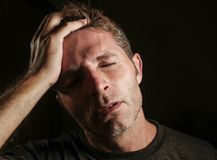 Young attractive and sad  man suffering depression and headache with hand on his tempo head in stress looking worried and sick iso Royalty Free Stock Photography