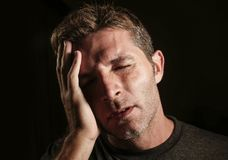 Young attractive and sad  man suffering depression and headache with hand on his tempo head in stress looking worried and sick iso Royalty Free Stock Image