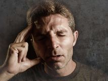Young attractive and sad  man suffering depression and headache with hand on his tempo head in stress looking worried and sick iso Royalty Free Stock Photos