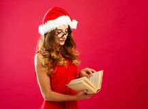 Young attractive Santa girl in red dress holding book over red b Royalty Free Stock Photos